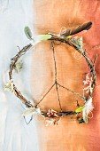 Peace sign made from twigs decorated with feathers and flowers