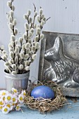 Easter still-life arrangement with willow catkins, daisies and Easter bunny cake tin
