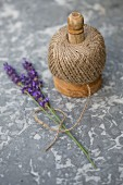 Ball of twine and sprigs of lavender on marble surface