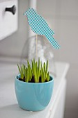 Bird hand-crafted from coloured paper and corrugated cardboard decorating blue pot of spring bulbs