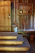 Steps leading up to door in rustic wooden house and old lattice window used as display case on wall