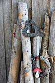 Heart-shaped wreaths and round twig wreath decorated with toadstool ornament hanging on logs leaning against wall