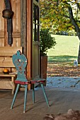Old wooden chair with rustic painted pattern in entrance of wooden house with view of sunny lawn and trees