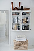 Collection of whiskies in wall-mounted cabinet above wicker trunk