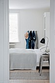 Jeans hanging from clothes pegs in white bedroom