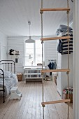 View into vintage-style child's bedroom through rope ladder