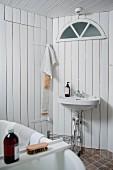 Waschbecken an einer Bretterwand mit Rundbogenfenster