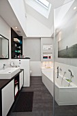 Washstand and fitted bathtub below skylight in renovated bathroom