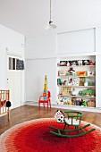 Grünes Retro Schaukelpferd auf rundem Teppich mit rotem Farbverlauf in Kinderzimmer