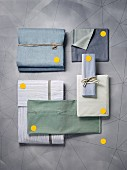 Various folded bedclothes in cool colours