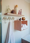 Towel hanging from hook next to rolled towels in shelf module below collection of vases on floating shelf