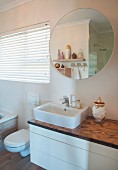 Washstand with white base unit and wooden top below round mirror