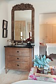 Holzkommode mit eingebautem Waschbecken, vor Wand mit Spiegel in holzgeschnitztem Rahmen, seitlich raumhoher Durchgang und Blick ins Schlafzimmer