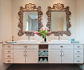 Washstand with twin sinks below mirrors with carved wooden frames