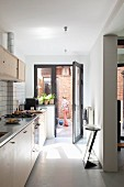 Fitted kitchen with designer bar stools and view of brick façade through open French window