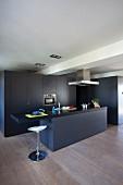 Schwarze raumhohe Kücheneinbauschränke mit passender Küchentheke und weißem Designer-Barhocker