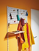 Coat rack made from perforated grid and colourful furniture knobs