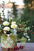 Autumn arrangement of creeping cotoneaster, white eustomas and crab apples in decorated tin