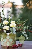 Herbstarrangement aus Zwergmispel, weißer Japanrose und Zieräpfeln in einer Dose mit Ornamenten