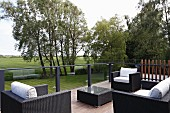 Black rattan outdoor furniture with white cushions on terrace with view across landscape