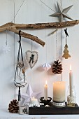 Christmas decorations hanging from rustic branch above lit candles in candlesticks