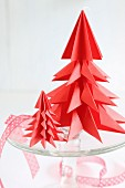 Red origami Christmas trees on glass cake stand