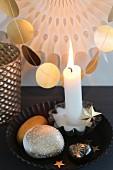 Brennende Kerze und gold angemalte Steine in schwarzer Kuchenform, vor Girlande aus goldenen Papierplättchen
