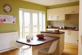 weiße Klassiker Schalenstühle vor Tisch mit Holzplatte, seitlich angebauter Schneideblock, in grün getönter Küche