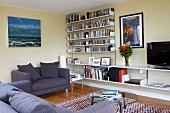 Dark grey sofa and white shelving system on yellow-painted wall in retro living room