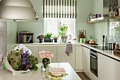Bouquet on table, L-shaped counter below window and kitchen utensils in white fitted kitchen
