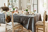 Table set for Easter breakfast with grey tablecloth and decorative wreaths on backrests of vintage chairs