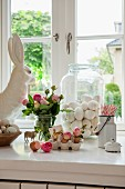 Romantic Easter arrangement on white windowsill; blown eggs in glass jar and bouquet of pink roses next to china rabbit