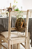 Hare figurine in wicker wreath hung on backrest of chair at table set for Easter celebration