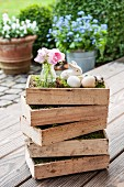 Pink posy in glass vase and Easter decorations in stacked wooden crates on wooden terrace