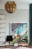 Modern artwork leant against pale grey wall behind vintage swivel chair and metallic pendant lamp