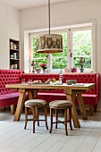 Button-tufted red bench below window and rustic dining table below owl-patterned pendant lamp in corner of dining room