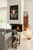 Fireplace, firewood store, rustic wooden side table and floor lantern on white wooden floor