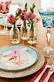 Romantic place setting with bird motif on plate and coloured crystal glasses next to roses in glass bottles