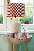 Table lamp with red and white zigzag lampshade and small framed mottoes on side table