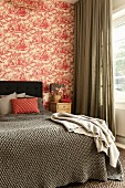 Blanket on double bed with headboard against wall with red and white toile de jouy wallpaper