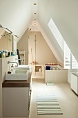 Spacious bathroom in converted attic; washstand with twin basins and bathtub under sloping ceiling