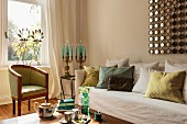 Biedermeier armchair below window, scatter cushions on sofa with loose cover and lit candles in candelabra in living room