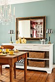 Antique mirror and table lamps on sideboard against pastel-blue wall: crystal chandelier and dining area in foreground