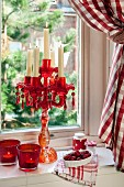 Red glass candelabra and tealight holders on windowsill with red gingham curtain