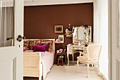 Antique-style double bed and dressing table against brown-painted wall