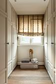 Fenster mit Raffrollo in schmaler Ankleide mit weißen Einbauschränke im Landhausstil