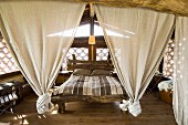 Bed frame made from plain wooden beams with linen curtains knotted at lower ends in rustic bedroom with
