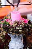 Wreath of hydrangeas, roses and elderberries encircling pink candle on candlestick