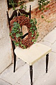 Wreath of wicker and ivy on chair against brick wall
