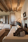 Elegant white sofa set in living room with wood-beamed ceiling